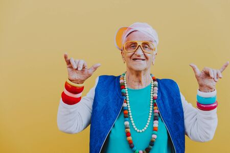 Funny grandmother portraits. 80s style outfit. trapstar dance on colored backgrounds. Concept about seniority and old people Standard-Bild - 132081422