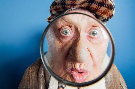 Lustige Porträts mit alter Großmutter. Ältere Frau als Ermittlerin mit der Lupe