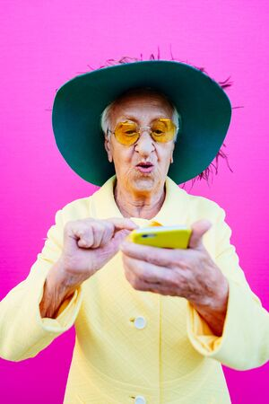 Funny grandmother portraits. Senior old woman, interacting with a smartphone. Concept about seniority