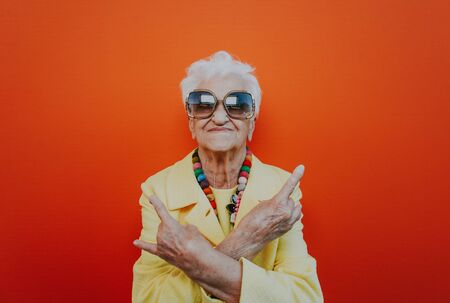 Funny grandmother portraits. Senior old woman dressing elegant for a special event. Rockstar granny on colored backgrounds 免版税图像