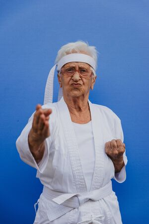 Funny grandmother portraits.granny fashion model on colored backgrounds. Karate master practicing martial arts