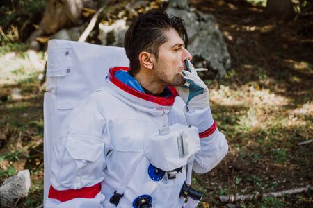 Astronaut exploring a new planet. Searching for a new home for humanity. Concept about science and nature. Smoking a cigarette during a break 写真素材