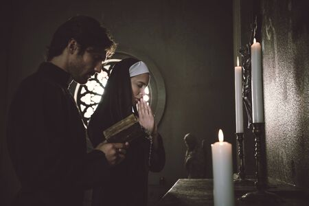 Nun and priest praying and spending time in the monastery 스톡 콘텐츠