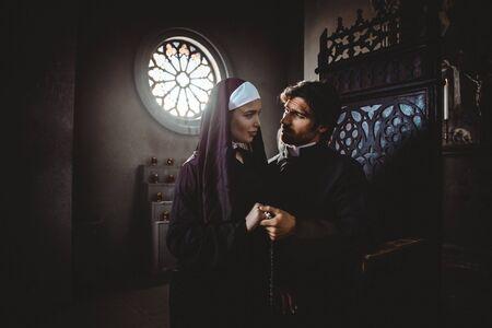 Nonne und Priester beten und verbringen Zeit im Kloster