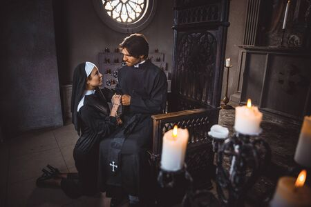 Nun and priest praying and spending time in the monastery Foto de archivo
