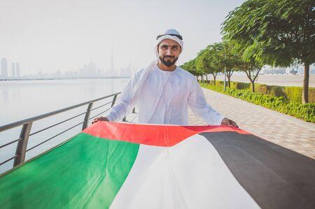 Man with traditional kandura holding the uae flag in Dubai