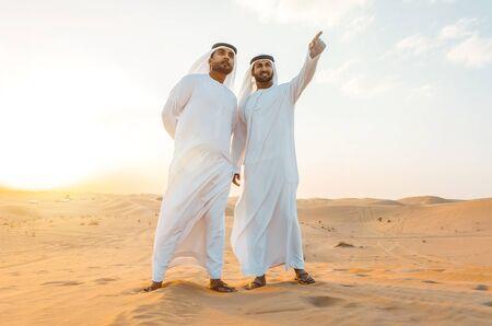 ドバイの砂漠で時間を過ごす伝統的なアラブ首長国連邦の白いカンドゥラを身に着けている2人のビジネスマン 写真素材