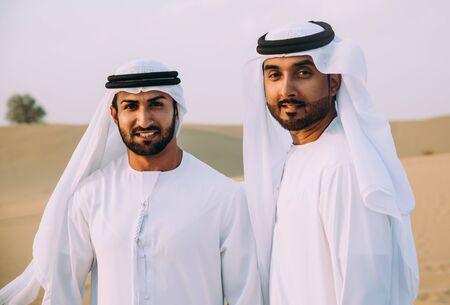 Two business men wearing traditional uae white kandura spending time in the desert of Dubai