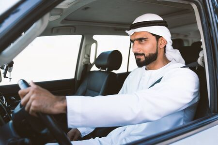 Handsome man with uae traditional outfit driving in Dubai. Middle eastern man with kandura in the car