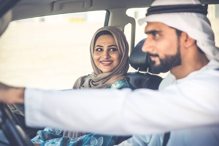 Happy couple driving the car in Dubai. Man and woman going out for shopping. Concept about relationship in the uae Stock Photo