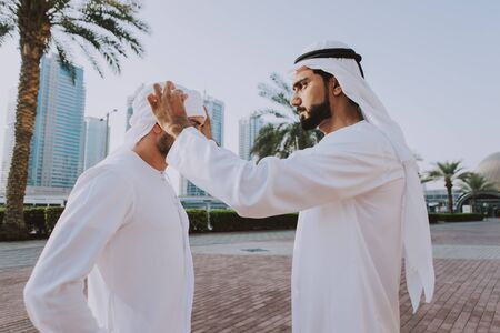 Two young businessmen going out in Dubai. Friends wearing the kandura traditional male outfit walking in Marina Stock fotó - 137878233