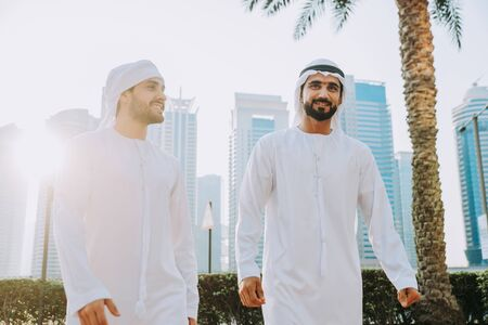 Two young businessmen going out in Dubai. Friends wearing the kandura traditional male outfit walking in Marina 版權商用圖片
