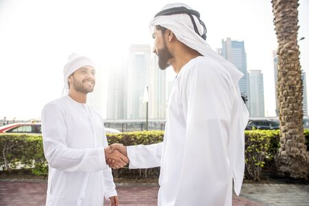 Two young businessmen going out in Dubai. Friends wearing the kandura traditional male outfit walking in Marina Stock fotó - 137878250