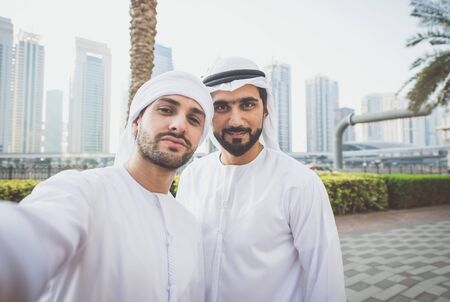 Two young businessmen going out in Dubai. Friends wearing the kandura traditional male outfit walking in Marina Stock fotó - 137878255