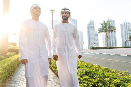 Two young businessmen going out in Dubai. Friends wearing the kandura traditional male outfit walking in Marina Stock fotó - 137878256