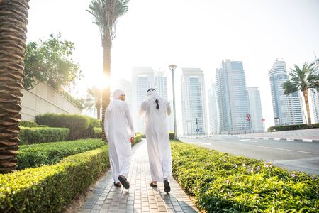 Two young businessmen going out in Dubai. Friends wearing the kandura traditional male outfit walking in Marina Stock fotó
