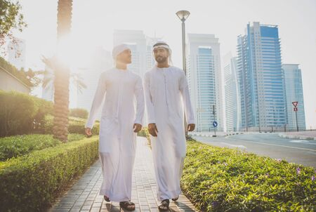 Two young businessmen going out in Dubai. Friends wearing the kandura traditional male outfit walking in Marina Stock fotó - 137878295