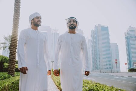 Two young businessmen going out in Dubai. Friends wearing the kandura traditional male outfit walking in Marina Stock fotó - 137878381