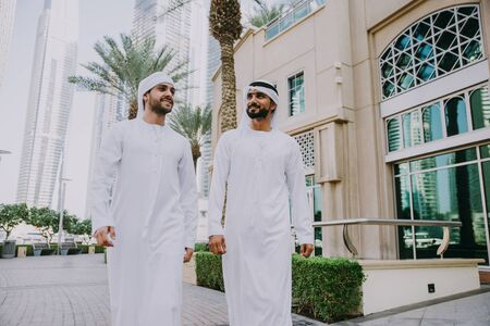 Two young businessmen going out in Dubai. Friends wearing the kandura traditional male outfit walking in Marina Stock fotó - 137878382