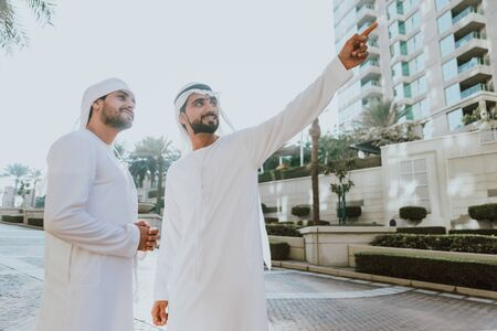 Two young businessmen going out in Dubai. Friends wearing the kandura traditional male outfit walking in Marina Stock fotó - 137878407