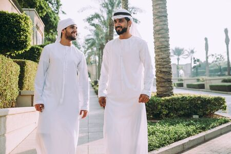 Two young businessmen going out in Dubai. Friends wearing the kandura traditional male outfit walking in Marina Stock Photo