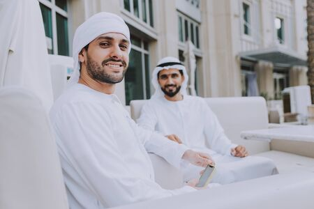 Two young businessmen going out in Dubai. Friends wearing the kandura traditional male outfit in Marina Stock fotó - 137878415