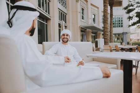 Two young businessmen going out in Dubai. Friends wearing the kandura traditional male outfit in Marina Stock fotó - 137878418