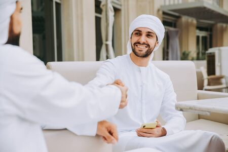Two young businessmen going out in Dubai. Friends wearing the kandura traditional male outfit in Marina Stock fotó - 137878419