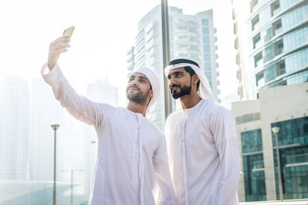Two young businessmen going out in Dubai. Friends wearing the kandura traditional male outfit in Marina Stock fotó - 137878430