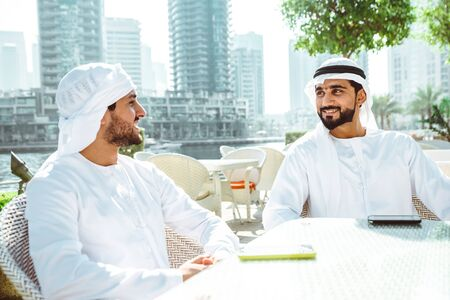 two young businessmen going out in Dubai. Friends wearing the kandura traditional male outfit in Marina Stock fotó - 137878602