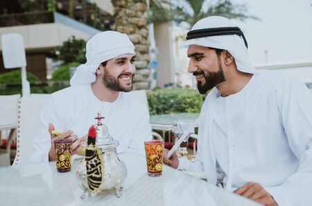 two young businessmen going out in Dubai. Friends wearing the kandura traditional male outfit in Marina