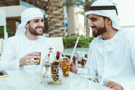 two young businessmen going out in Dubai. Friends wearing the kandura traditional male outfit in Marina Stock fotó - 137878610