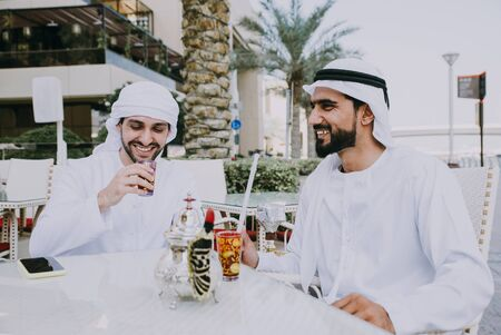 two young businessmen going out in Dubai. Friends wearing the kandura traditional male outfit in Marina Stock fotó - 137878611