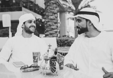 two young businessmen going out in Dubai. Friends wearing the kandura traditional male outfit in Marina Stock fotó - 137878615