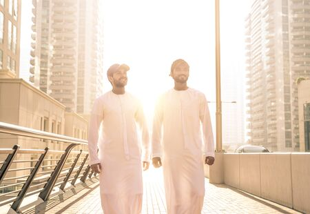 Two young men going out in Dubai. Friends wearing the kandura traditional male outfit and baseball hat in Marina Stock Photo