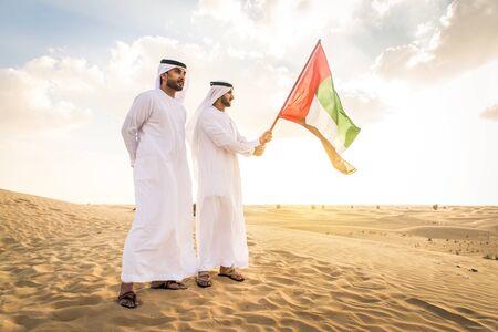 Arabische Männer mit Kandora, die in der Wüste spazieren - Porträt von zwei Erwachsenen aus dem Nahen Osten mit traditioneller arabischer Kleidung
