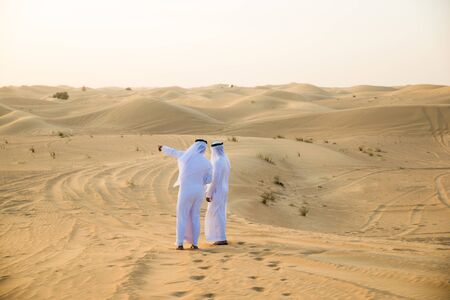 Arabische Männer mit Kandora, die in der Wüste spazieren - Porträt von zwei Erwachsenen aus dem Nahen Osten mit traditioneller arabischer Kleidung Standard-Bild