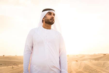 Arabian men witk kandora walking in the desert - Portrait of two middle eastern adults with traditional arabic dress