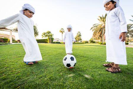 Groupe d'enfants du Moyen-Orient portant une kandora blanche jouant dans un parc à Dubaï - Joyeux groupe d'amis s'amusant à l'extérieur aux Émirats arabes unis