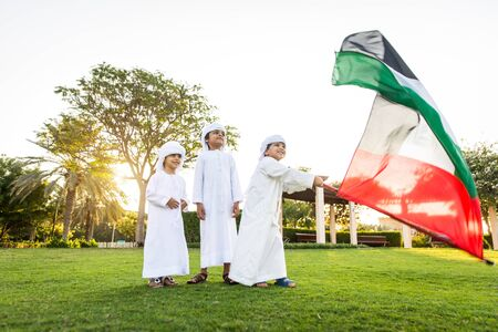 Group of middle-eastern kids wearing white kandora playing in a park in Dubai - Happy group of friends having fun outdoors in the UAE Stock Photo
