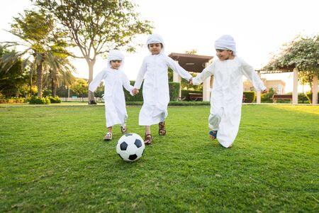 Gruppe nahöstlicher Kinder, die weiße Kandora tragen, die in einem Park in Dubai spielen - Glückliche Gruppe von Freunden, die sich im Freien in den Vereinigten Arabischen Emiraten amüsieren