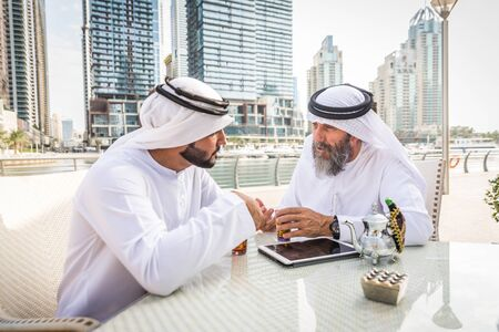 Two businessmen with traditional emirates clothes meeting in Dubai - Senior and young adults having business in the UAE Reklamní fotografie