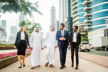 Multiethnische Gruppe von Menschen bei einem Geschäftstreffen in den Vereinigten Arabischen Emiraten - Geschäftsleute, die im Freien spazieren gehen und über Geschäfte sprechen