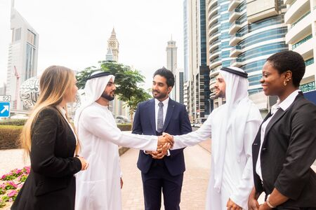 Multi-ethnic group of people on a business meeting in the UAE - Business people walking outdoors and talking about business