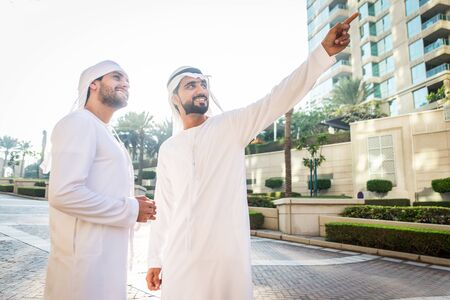 Middle-eastern young adults wearing kandora walking outdoors in Dubai - Two businessmen meeting outdoors