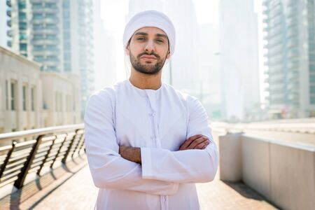 Middle-eastern young adult wearing kandora walking outdoors in Dubai - Arabic man wearing the traditional emirates clothes