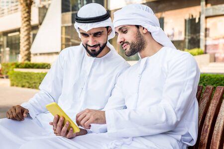 Junge Erwachsene aus dem Nahen Osten, die Kandora tragen, gehen in Dubai im Freien spazieren - Zwei Geschäftsleute treffen sich im Freien