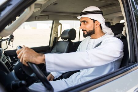 Handsome arabic man driving a car