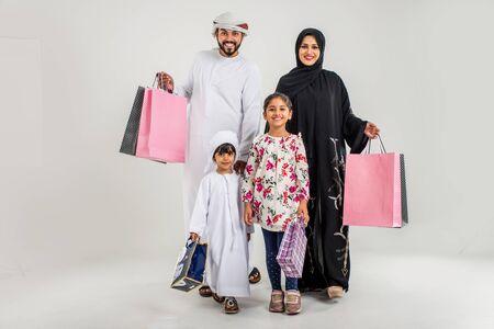 Famille du Moyen-Orient avec des robes traditionnelles des émirats posant dans un studio photographique - Concepts sur le mode de vie, le bonheur et les relations familiales aux Emirats Arabes Unis