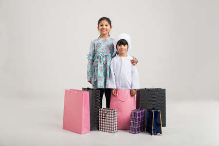 Middle eastern family with traditional emirates clothes with shopping bags